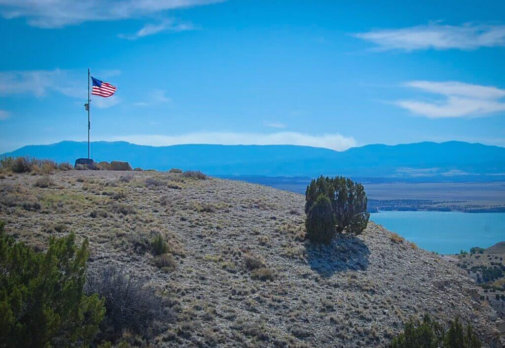 An American flag flying on top of a mountain that overlooks Pueblo Reservoir camping site.