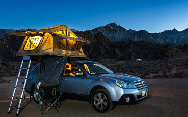 An awesome car camping experience with the tent on the roof of the SUV and it's glowing in the blue light of dusk with mountains and a dark sky fading in the background.
