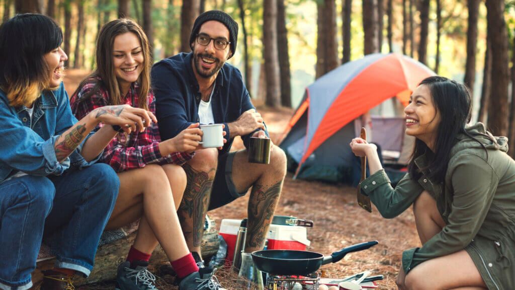A group of 4 friends laughs around a campfire at their car camping site while breakfast cooks and they sip on coffee.