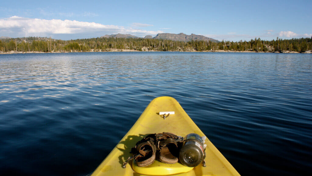 A yellow kayak glides along calm blue water in Blue Ridge Reservoir in Arizona with trees and mountains in the background.