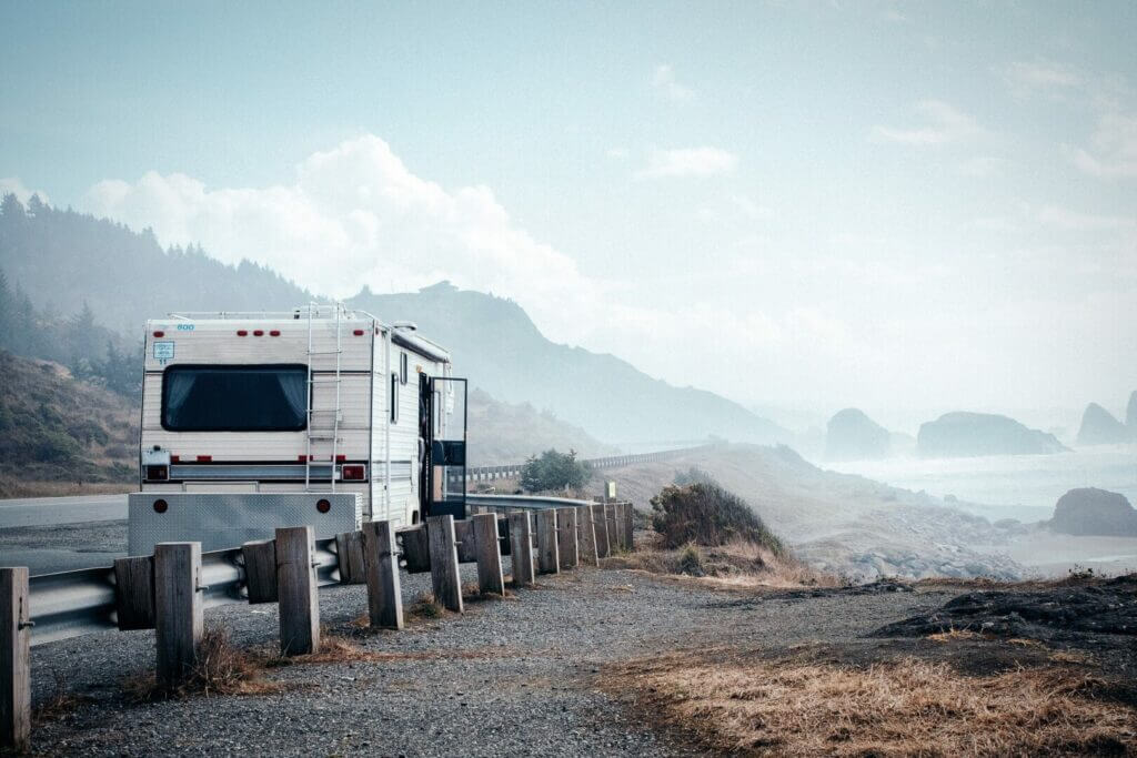 RV parked on the side of the road with the beach on the background and some fog. You can find places to park your RV for free like this on Campendium.