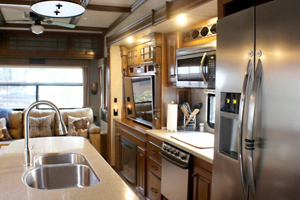 Interior of a fifth wheel RV. The kitchen, fridge, microwave are in the foreground with the couch and TV in the background.
