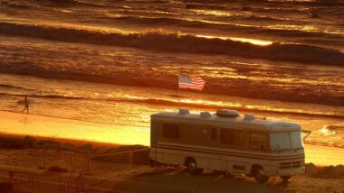 RV on beach flying a USA flag