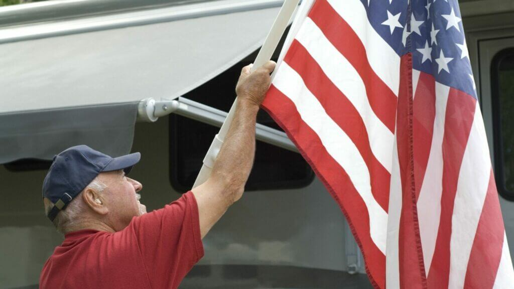 Man putting up RV flag pole with US flag while camping in his RV