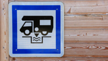 Blue and white RV dump station sign on light wood grain wall to dump dirty grey water safely.