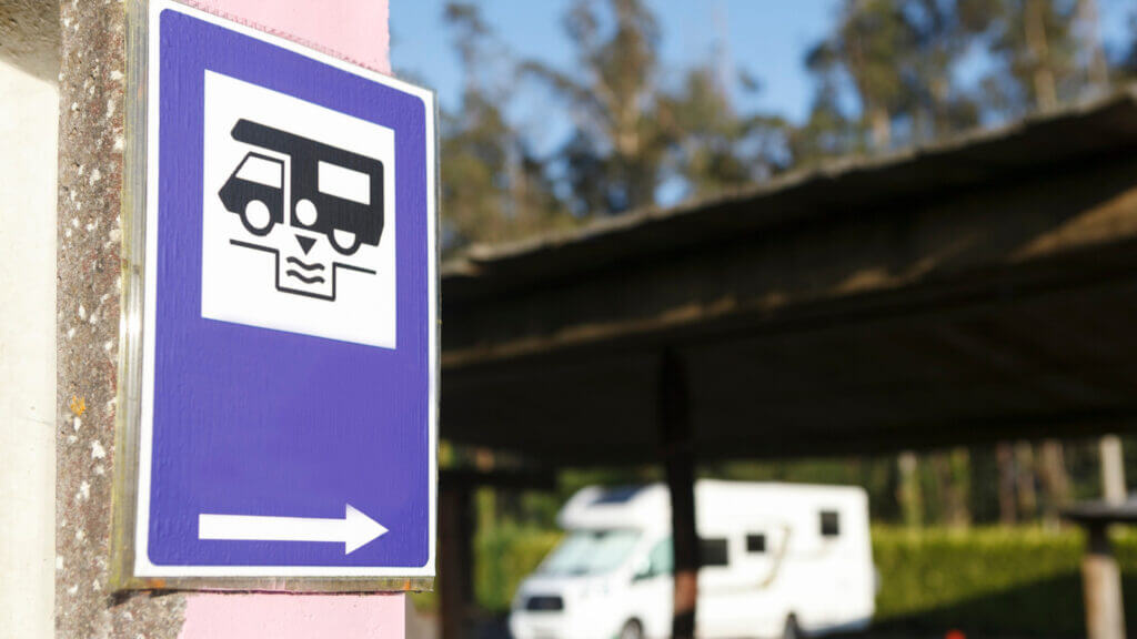 A blue and white sign points to a dump station to drain an RV's grey water and sewage.