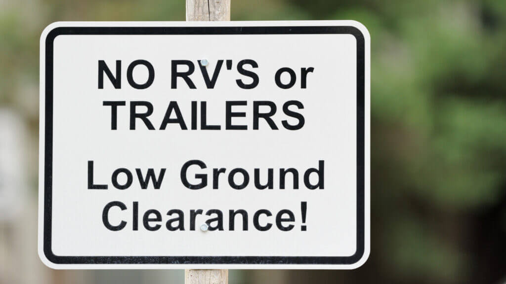 "A white sign that says ""No RV's or trailers - low ground clearance!"" with greens in the background."
