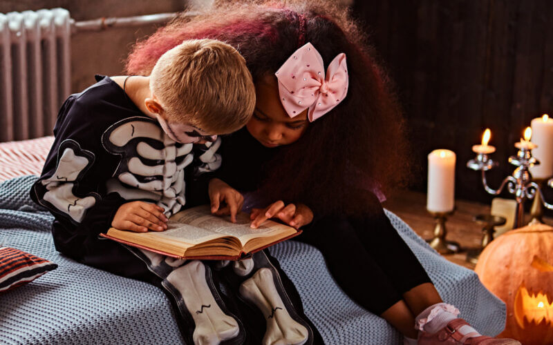 A boy dressed as a skeleton and a girl with a bow in her hair are reading spooky stories for kids next to some spooky halloween candles.