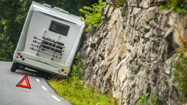 An RV is pulled off the road and against a rock wall with a safety cone in the road behind it. Is RVing safe?