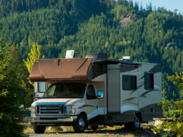 A tall RV is parked in a forest. Do you know how tall your RV is?