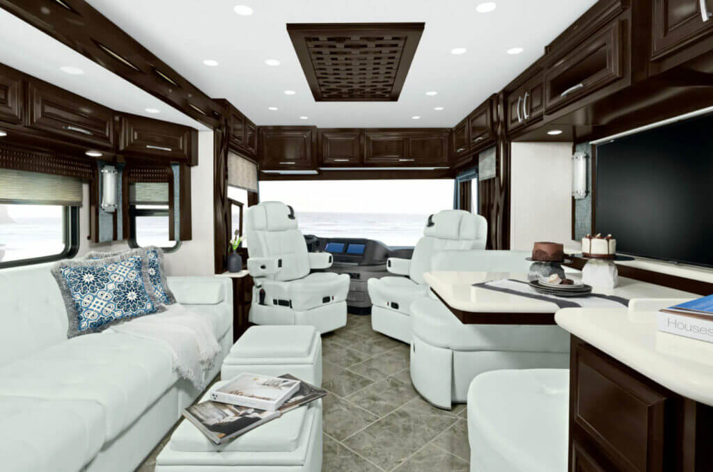Interior shot of a Newmar RV motorcoach with white couches and chairs, and brown cabinets. Winnebago owns Newmar RV.