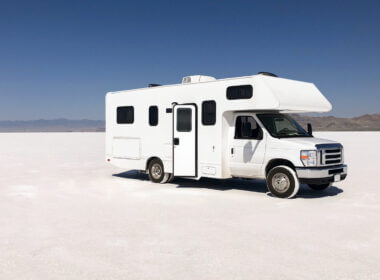 A white self-contained RV is parked in the middle of nowhere white desert, but they don't have to worry! They have everything they need onboard so they don't have to rely on campsite hookups to use the bathroom or shower.