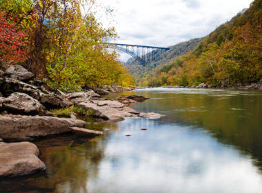 New River Gorge on a fall day with a reflective river, colorful leaves along the shore, and the iconic bridge around the bend.