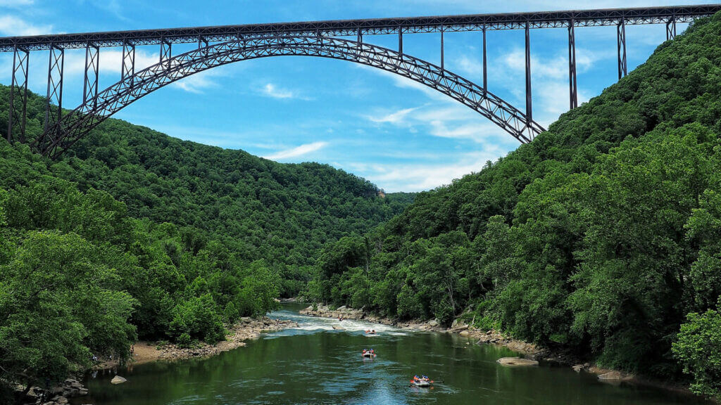 On a summer day rafters navigate the rapids in the New River Gorge national park under the iconic bridge.
