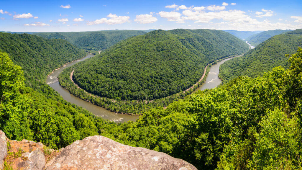 The New River Gorge is the newest National Park in West Virginia and its huge picturesque park is pictured here. Green foliage is abundant alongside the winding New River.