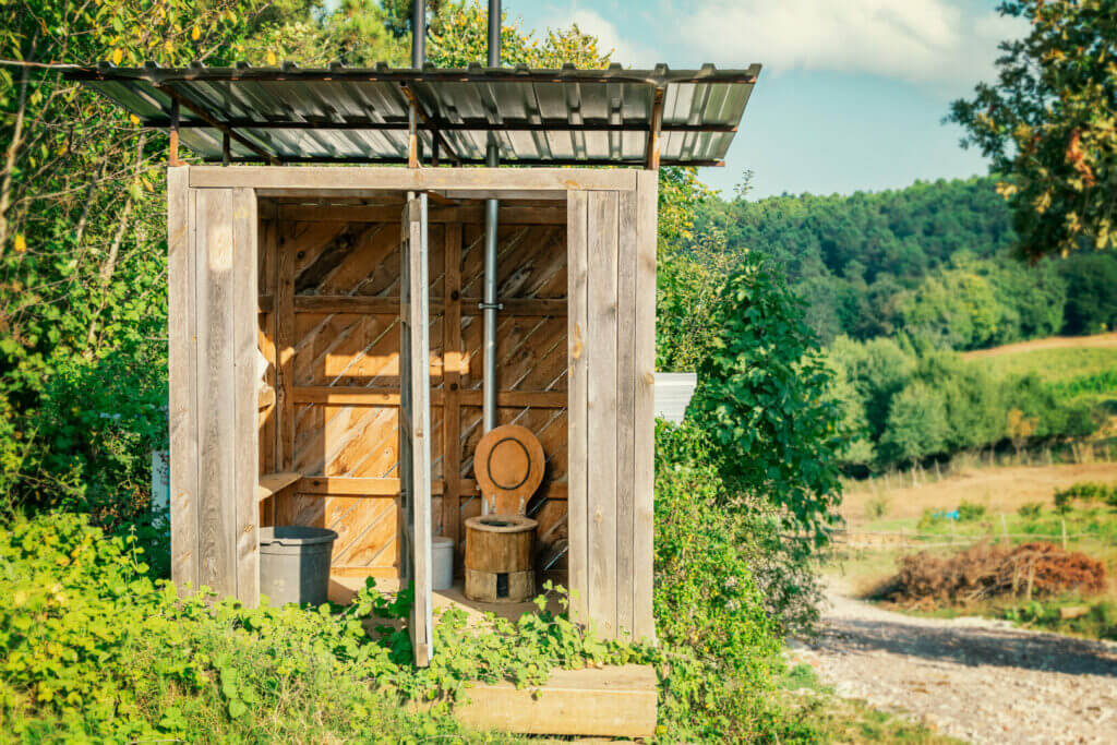 Wooden shed in nature with an ecological composting toilet inside. When using a composting toilet for RV, you can relieve yourself in nature!