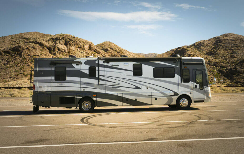 Class A RV in an empty parking lot with mountains in the background. You need to figure out which RV you want when figuring out how much to rent an RV.