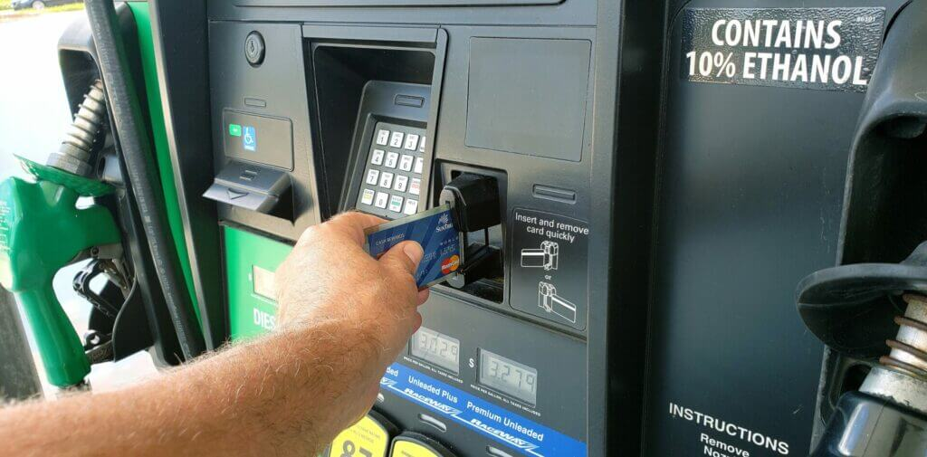 Man at a gas pump putting his credit card in the payment slot. Buying fuel is something to think about when planning how much to rent an RV.