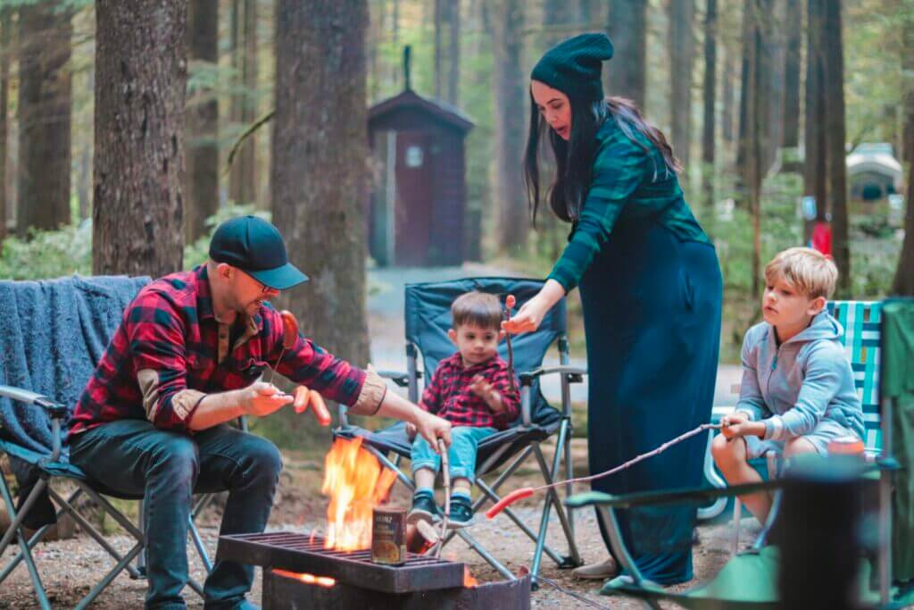 Family cooking hotdogs on sticks over an open campfire. They found out how much to rent an RV was and headed out on a vacation.