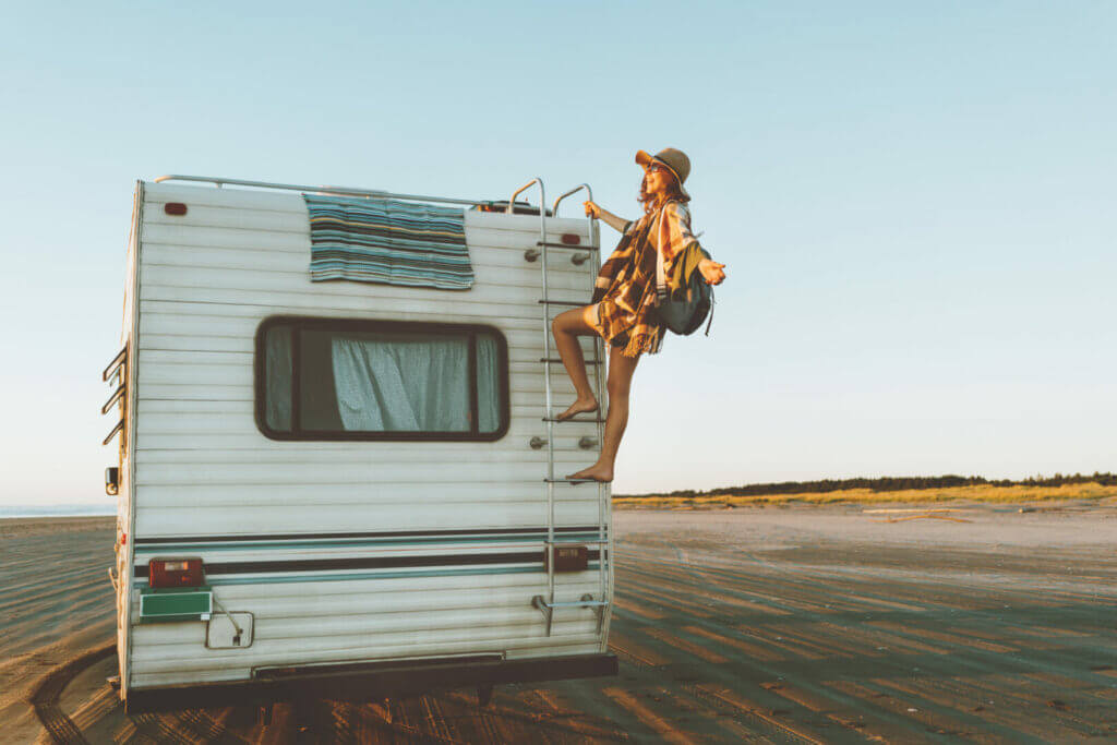 Woman hanging off her RV ladder smiling into the sun