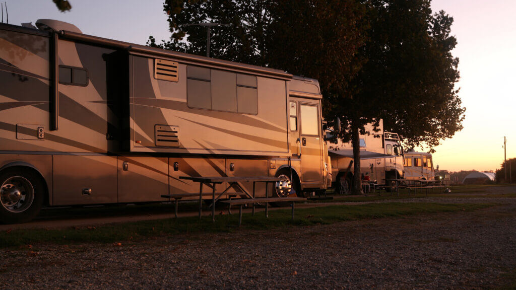 A nice RV park gets dark with the sunsetting on the parked RVs.