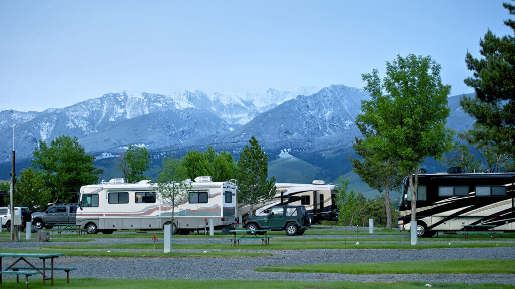 A sparse RV park set against beautiful snowy mountains.