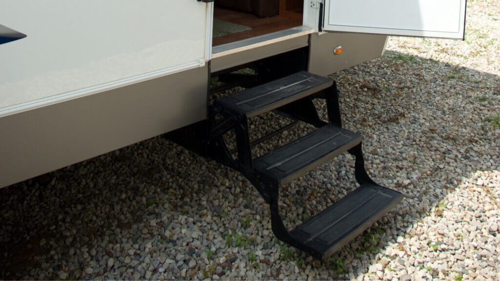 RV steps are lowered for ease of access into the RV while stationed at the campsite.