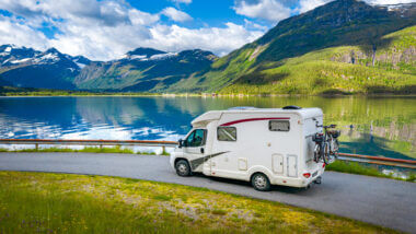 An RV drives along a roadway set against a lake and green and blue mountains.