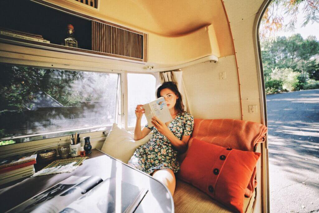 Woman reading a book in an RV. There are good and bad things about RV living.