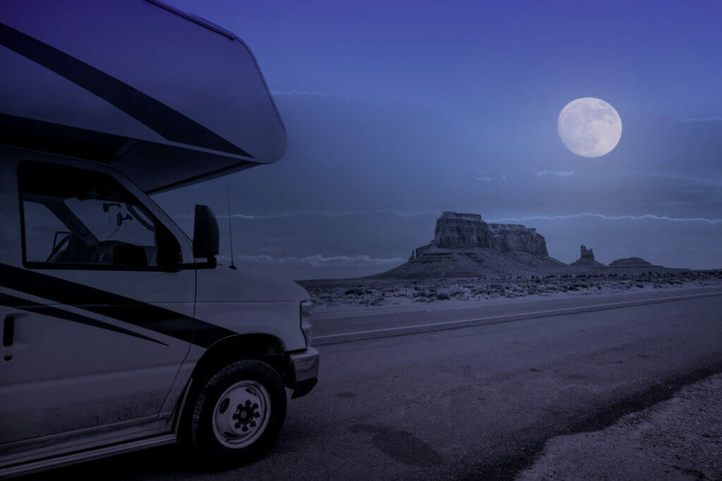 parking recreational vehicle in monument valley at full moon night, Arizona, USA. When you ask what is boondocking, picture yourself here.