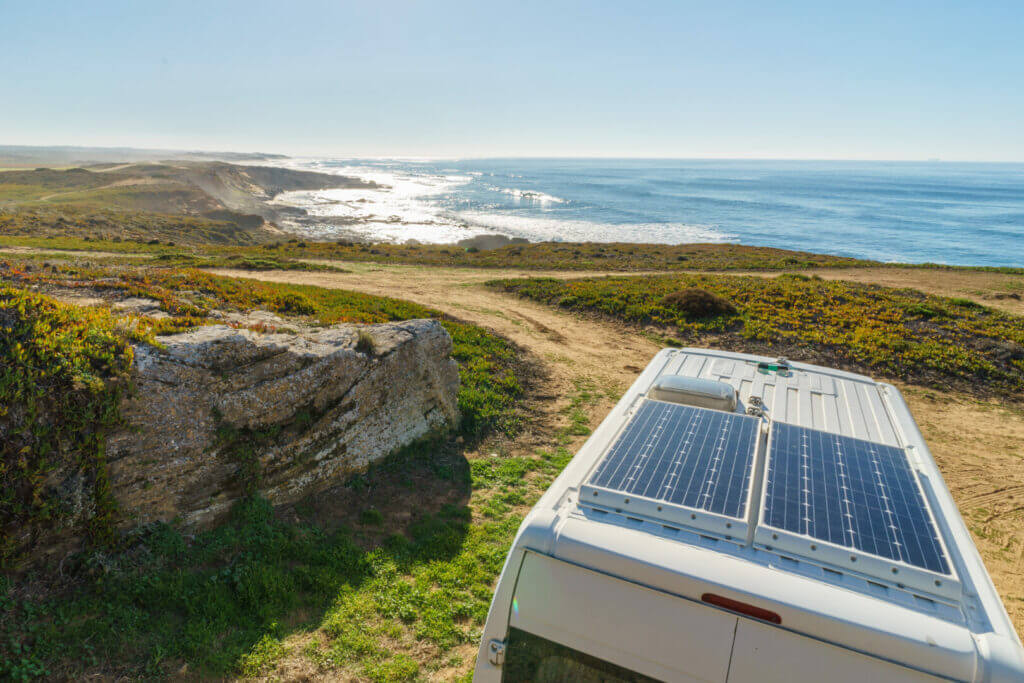 RV with solar panels on the roof on the beach, this is an important you need to consider when you ask yourself what is boondocking