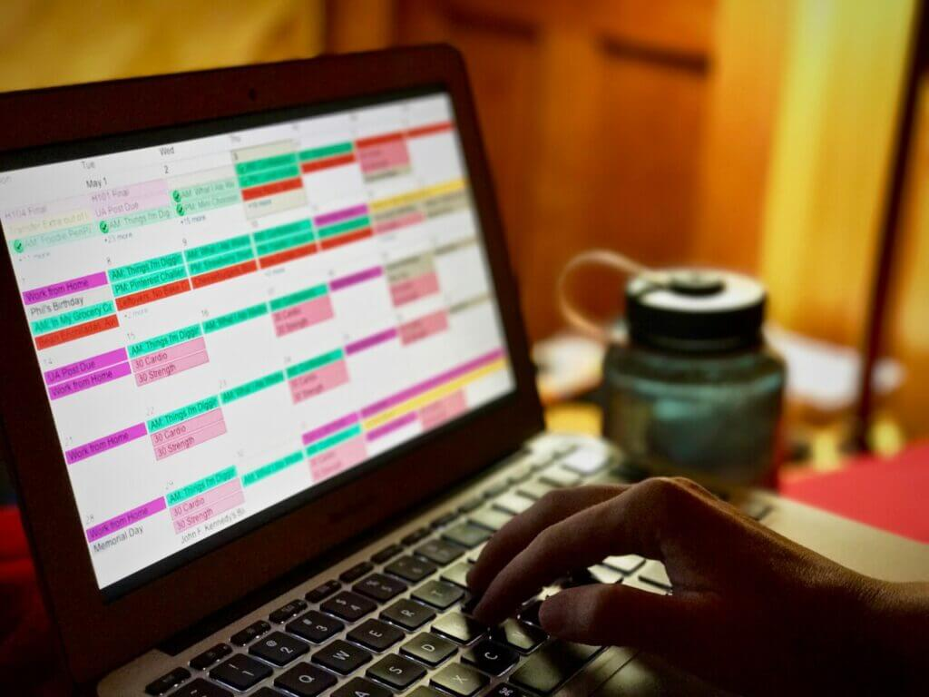 A hand on a laptop keyboard with a full calendar on the screen. You can work while traveling if you're organized.