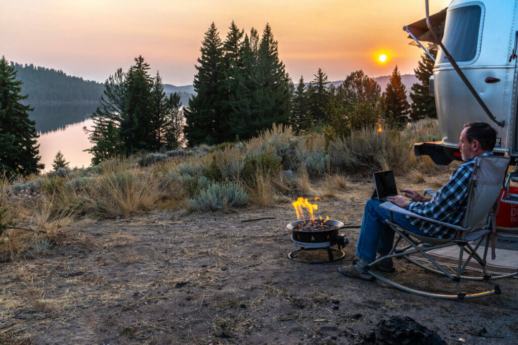 Person sitting on a rocking chair by the side of a travel trailer RV with a campfire working on a laptop as the sun setting over a distance hill. He can work while traveling because she practices good productivity tips.
