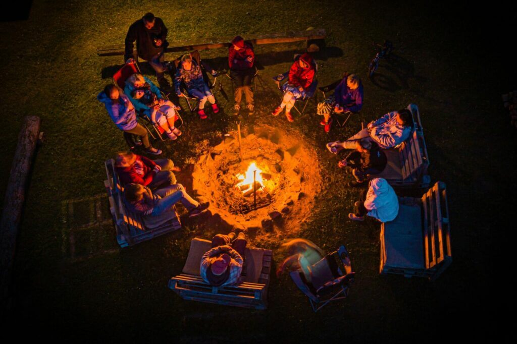 Drone shot of a family sitting around a campfire. It's proper campground etiquette to keep noise down after quiet hours.
