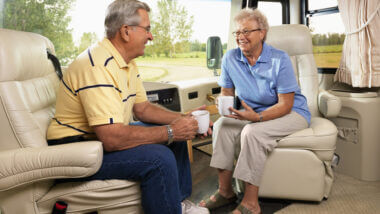An older couple sit comfortably in their RV recliners and relax while drinking coffee.