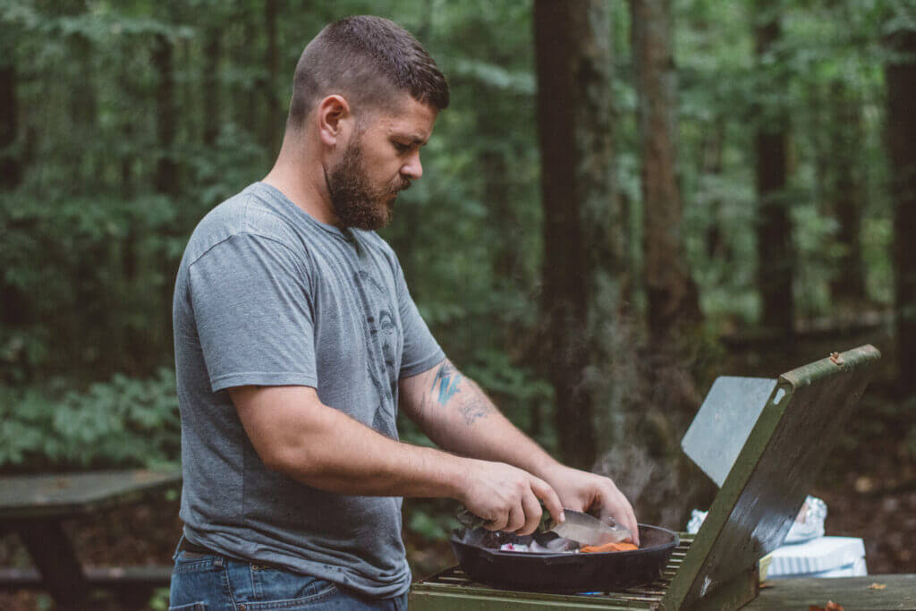 Man cooking on a portable grill outside in the woods