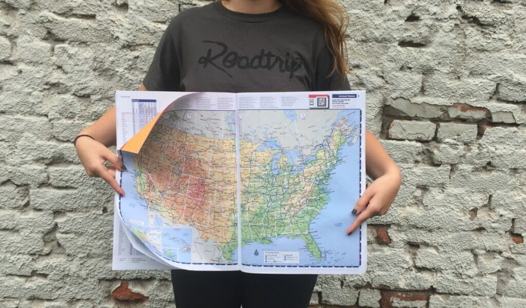 Girl holding US map with major interstates on it for use when planning a road trip