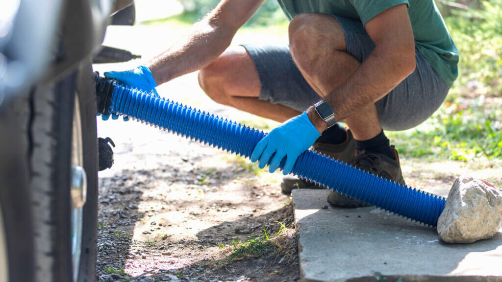 Man connecting his RV sewer hose to his RV. Learn how to use an RV dump station here.