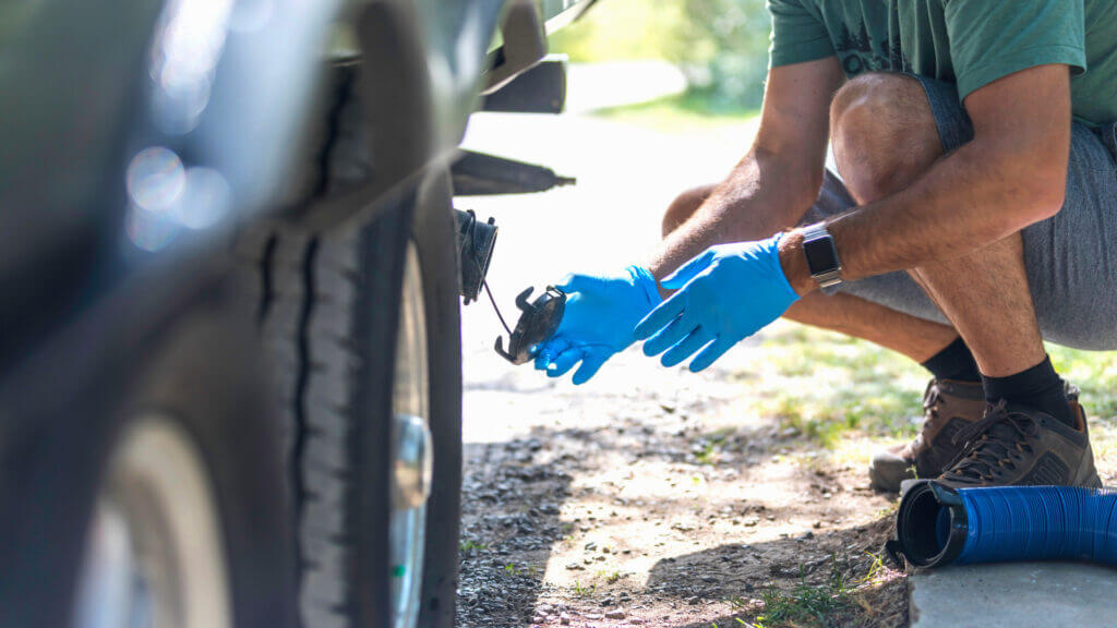 Man putting the sewer cap back on his RV hose. Learn how to use an RV dump station like a pro.