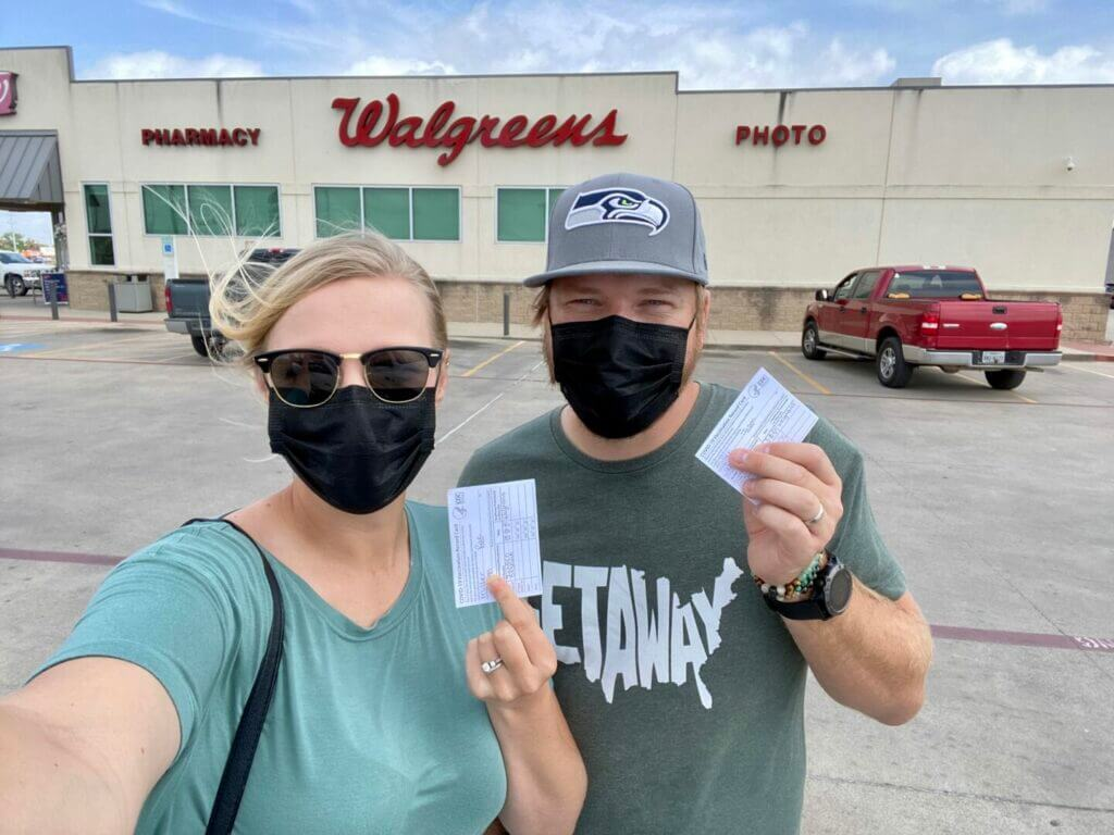 Couple standing in front of Walgreens holding up their COVID vaccination cards.
