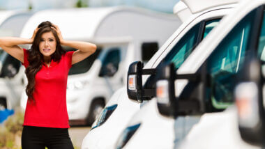 A woman with a red shirt stands in front of a row of RVs and she looks very stressed. Is 2021 the worst year to buy an RV?