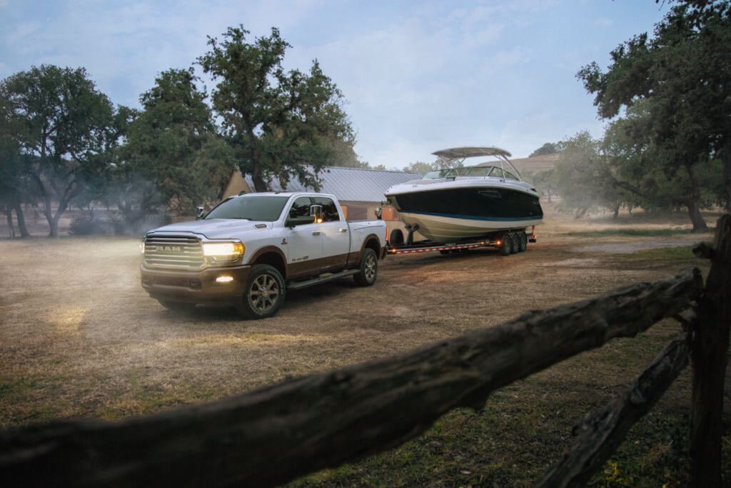A white Dodge Ram 2500 tows a boat on a dusty road.