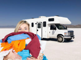 A woman holds a stack of laundry in front of an RV parked in the desert. She can use one of the best portable washing machines anywhere she parks in her tiny space!