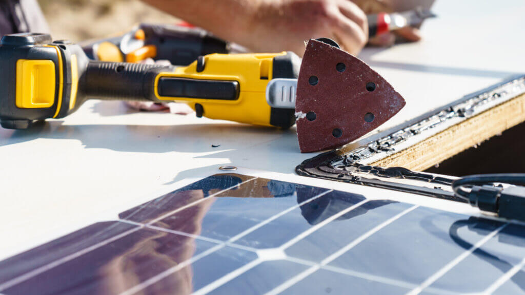 A close up of a solar panel being installed on the roof of an RV with the sander and tools in the background.