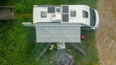 An overhead view of an RV camped out with solar panels on the roof. The awning is rolled out and a woman is sitting in a chair around a fire pit.