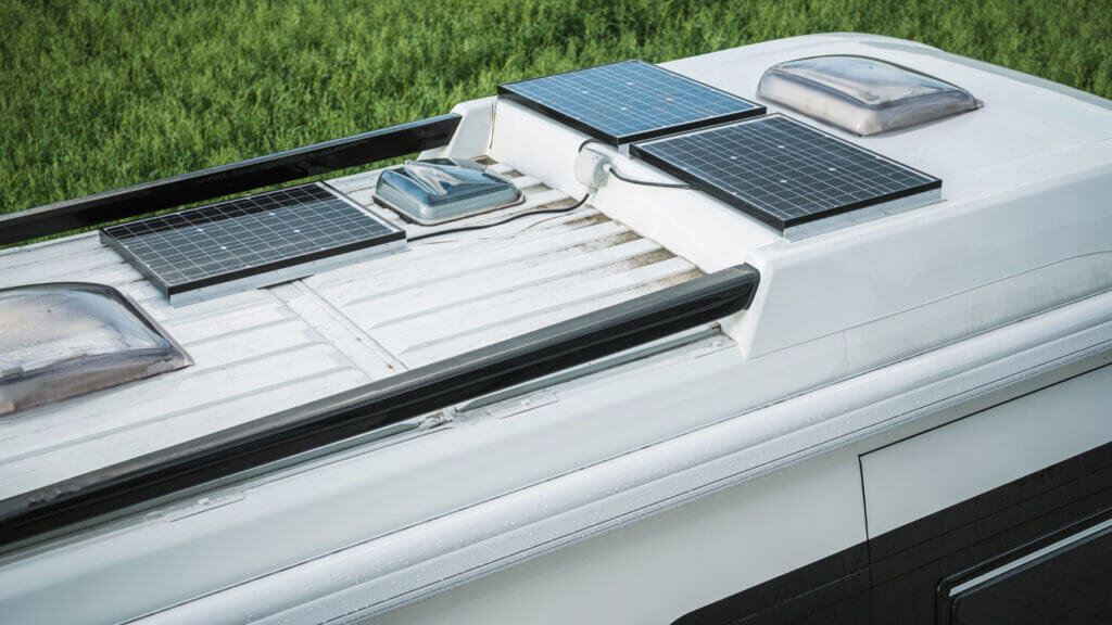 A close up of an RV roof with 3 solar panels installed on the roof. How much does it cost to install solar panels on an RV?