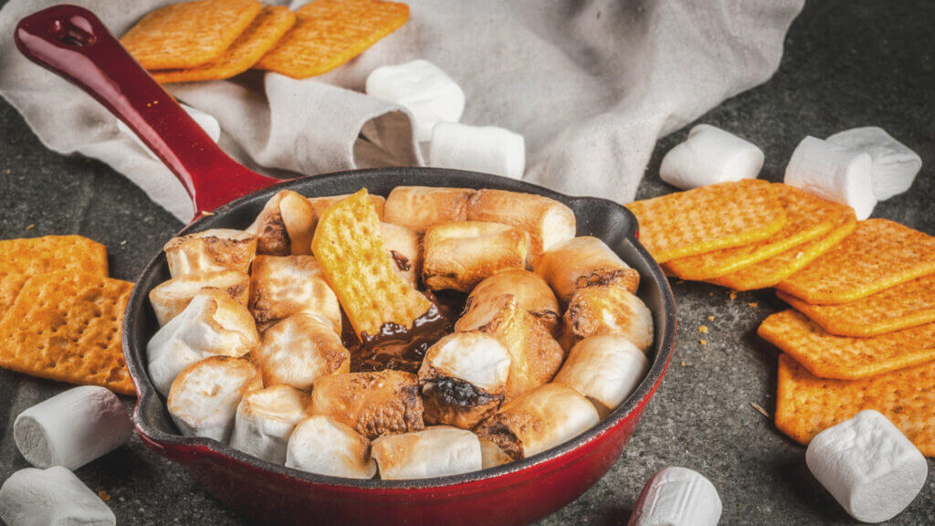 A skillet is full of melted chocolate and marshmallows with a pile of graham crackers nearby to dip into the melty deliciousness.