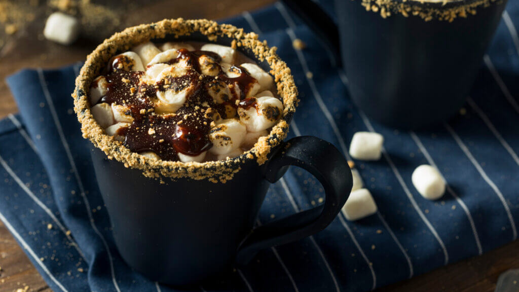 A blue cup is filled with smores goodness, with a graham cracker rim and marshmallows and melted chocolate covering the top.