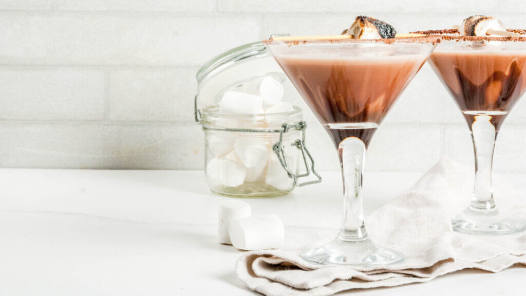 Two martini glasses are filled with the best smore martini recipe and topped with a roasted marshmallow with a jar of marshmallows spilling nearby.