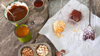 A gourmet spread of the best smore recipes with chocolate, candy bars, marshmallows, coconut flakes, almonds, and graham cracker crumbs.